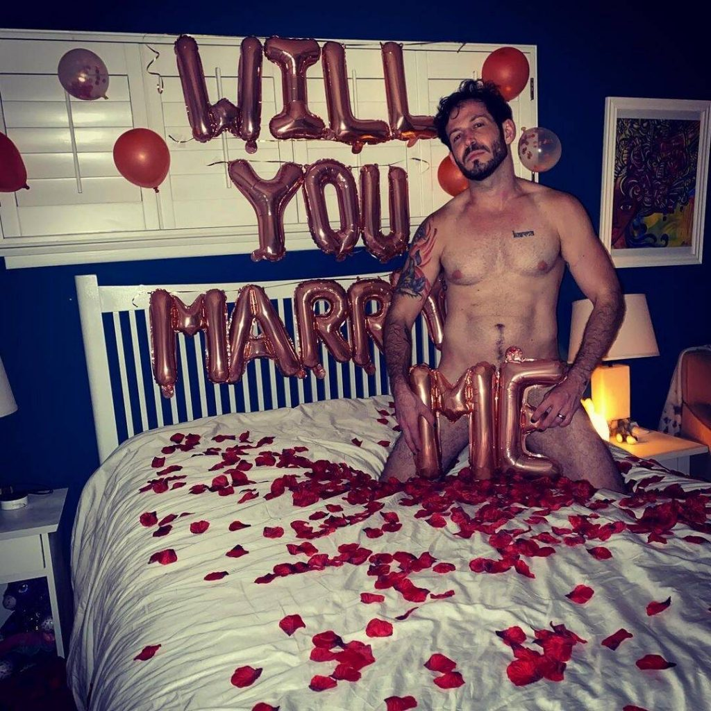 demande en mariage homme tout nu dans un lit avec des petales de roses et des ballons gonflables