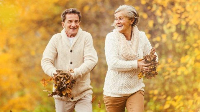 Couple De Personnes Âgées Qui Se Court Après Avec Des Feuilles D'arbres En Mains