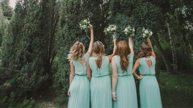 Demoiselles D'honneur En Robes Vertes De Dos Qui Lèvent Leurs Bouquets