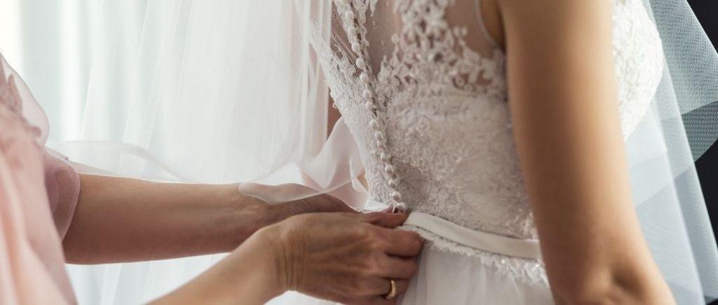 Femme De Dos En Robe De Mariée Avec Quelquun Qui Ferme Sa Robe