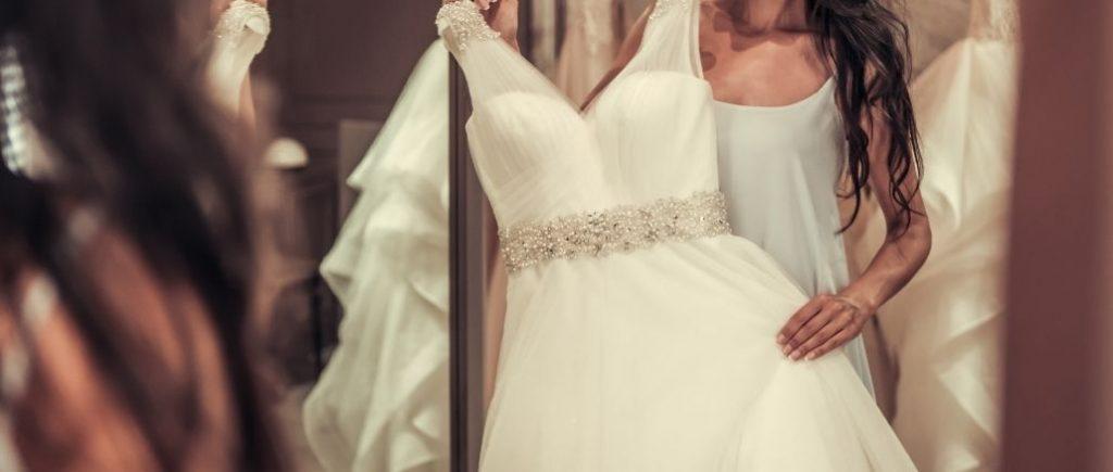 Femme Qui Se Tient Devant Un Miroir Avec Une Robe De Mariée Devant Elle