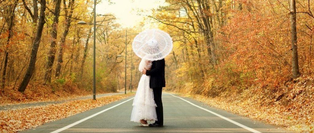 Mariés Cachés Par Une Ombrelle Au Milieu Dune Route Entourés Par Des Arbres En Automne