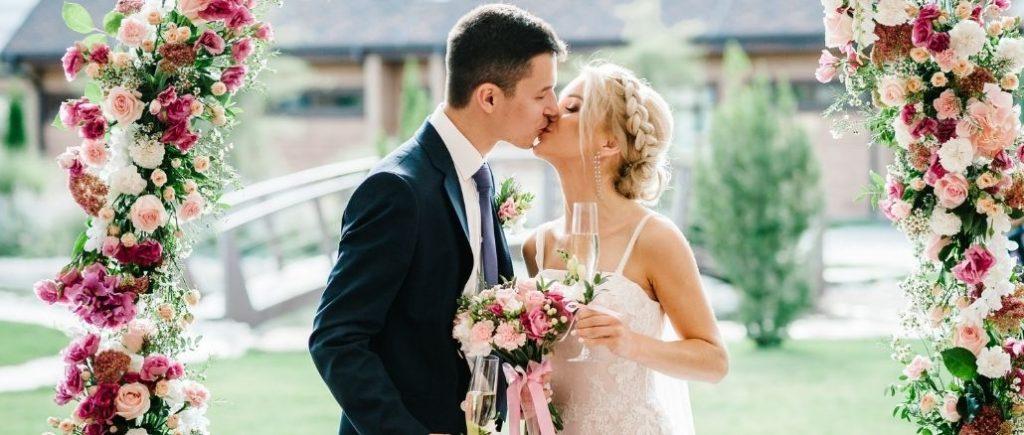 Organiser Le Mariage Parfait Couple Qui Sembrasse Sous Une Arche De Fleurs